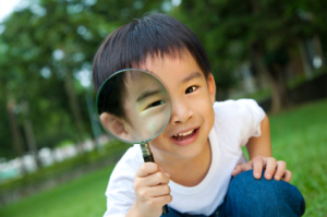 happy kid with magnifying glass